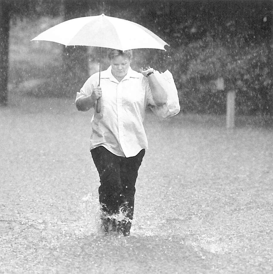 Mary McDonald trudges along a water-covered roadway carrying groceries home in the Longford Edition, Little Cypress community along Texas 87. (Photo taken 5/18/1989) Photo: Enterprise File