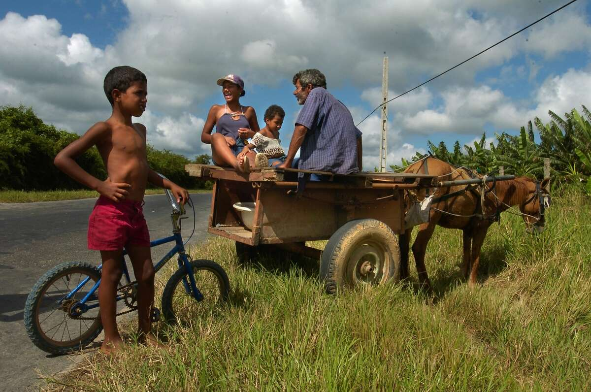 A family travels by horse and cart on a country road in the province of Pinar del Rio in western Cuba. Illustrates TRAVEL-CUBA (category t) by Rosemary McClure (c) 2006, Los Angeles Times. Moved Tuesday, Jan. 24, 2006. (MUST CREDIT: Los Angeles Times photo by Gail Fisher.)