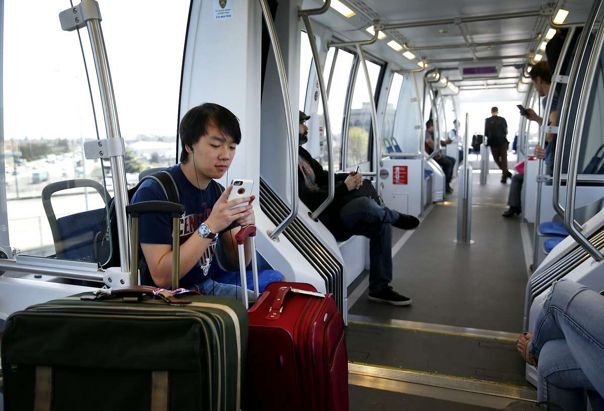 Brandon Mah travels with two large pieces of luggage on the BART Oakland Airport Connector line on his way to catch a flight in Oakland, Calif. on Friday, March 18, 2016.