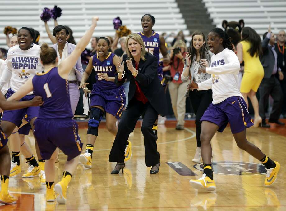 Albany head coach Katie Abrahamson-Henderson (center) and her players swarm the court celebrate their 61-59 win over Florida in a first-round NCAA Tournament game on Friday. Photo: Mike Groll, AP