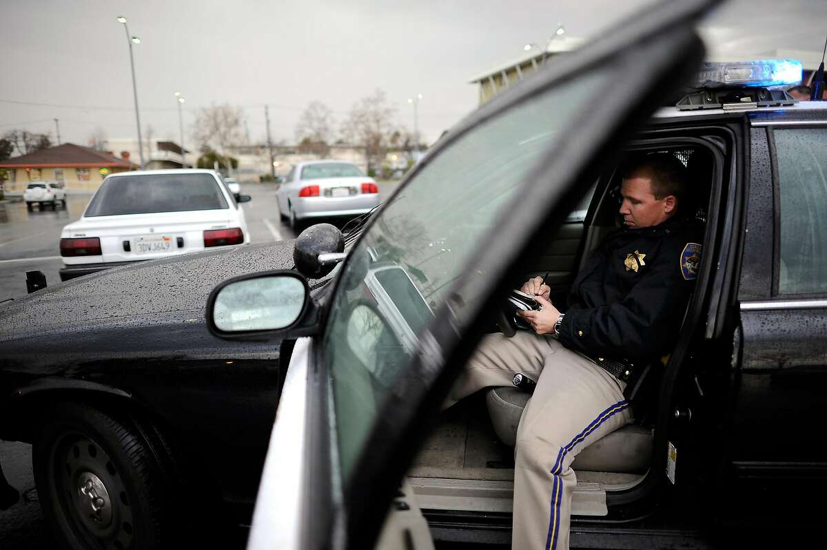 A California Highway Patrol offficer sits in his cruiser during a traffic stop. A new state report concludes that Black and Latino drivers were stopped and searched more often that whites in 2019.