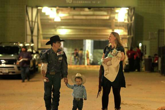 Bareback rider Ryan Gray leaves NRG Stadium with his two-year-old son Ransom, his wife Lacy, and their one-month-old daughter Laramie after the rodeo, Tuesday, March 15, 2016, in Houston.