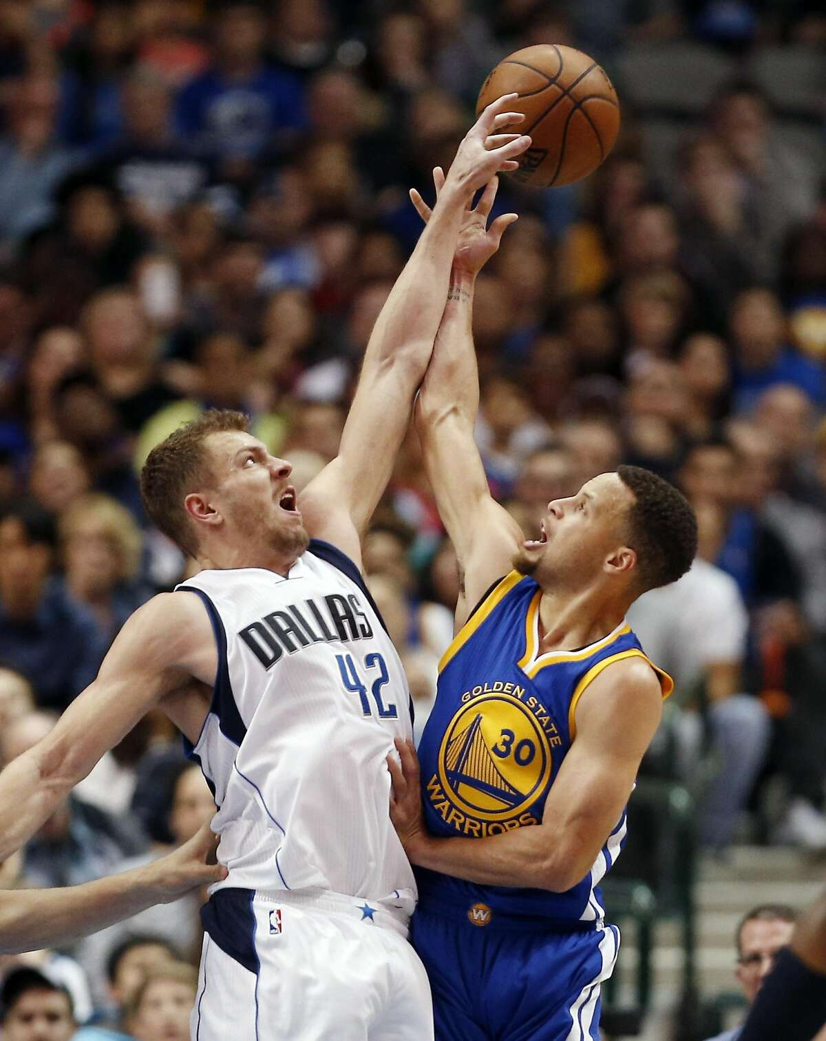 Dallas Mavericks forward David Lee (42) blocks a shot by Golden State Warriors guard Stephen Curry (30) during the first half of an NBA basketball game Friday, March 18, 2016, in Dallas. (AP Photo/Brandon Wade)
