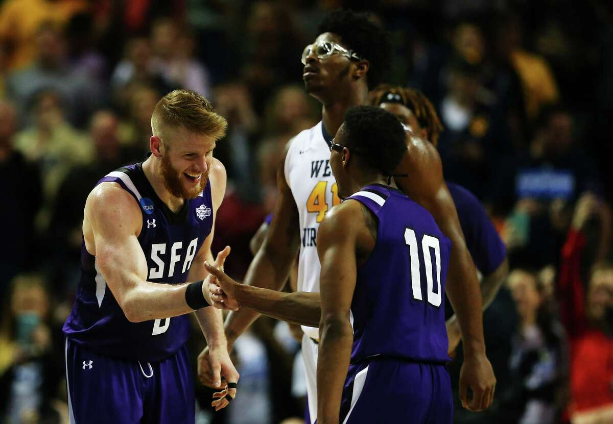 NEW YORK, NY - MARCH 18: Thomas Walkup #0 and Trey Pinkney #10 of the Stephen F. Austin Lumberjacks celebrate defeating the West Virginia Mountaineers 70-56 during the first round of the 2016 NCAA Men's Basketball Tournament at Barclays Center on March 18, 2016 in the Brooklyn borough of New York City.
