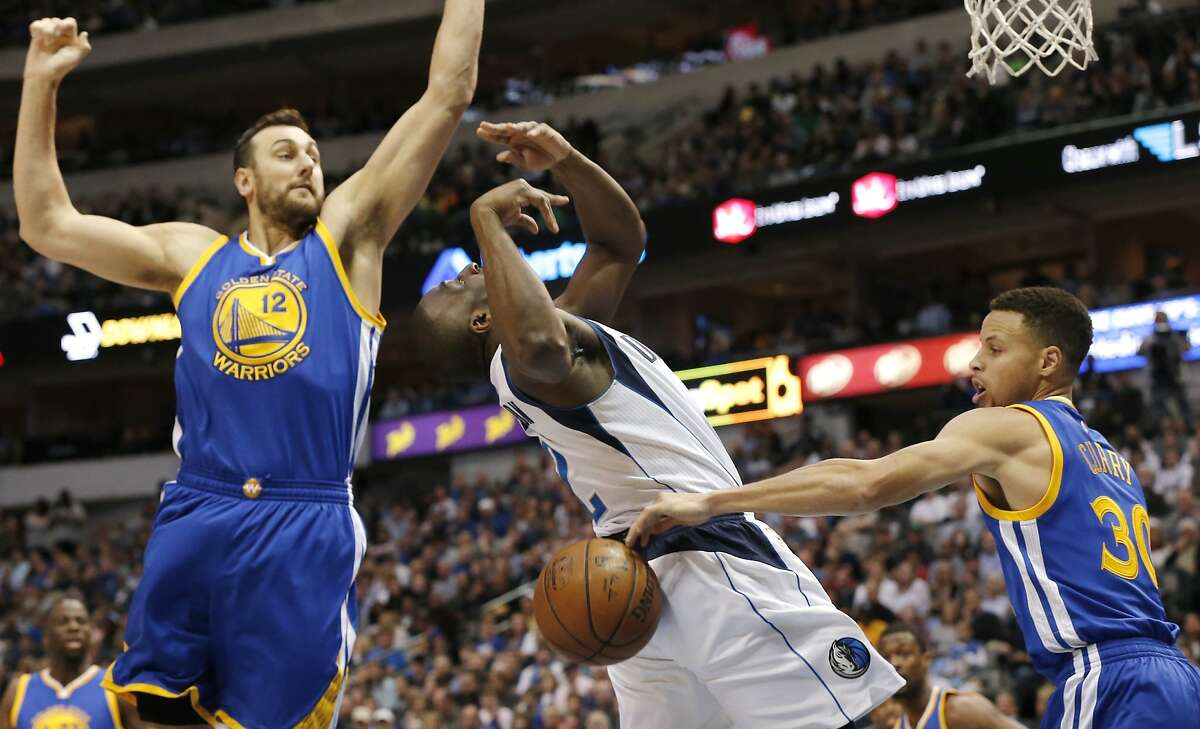 Golden State Warriors forward Andrew Bogut (12) looks on as guard Stephen Curry, right, strips the ball from Dallas Mavericks guard Raymond Felton (2) during the first half of an NBA basketball game Friday, March 18, 2016, in Dallas. (AP Photo/Brandon Wade)