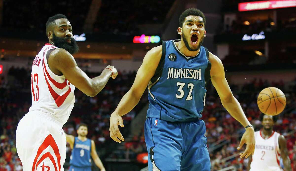 HOUSTON, TX - MARCH 18: Karl-Anthony Towns #32 of the Minnesota Timberwolves reacts to a call in front of James Harden #13 of the Houston Rockets on the court during their game at the Toyota Center on March 18, 2016 in Houston, Texas. NOTE TO USER: User expressly acknowledges and agrees that, by downloading and or using this Photograph, user is consenting to the terms and conditions of the Getty Images License Agreement.