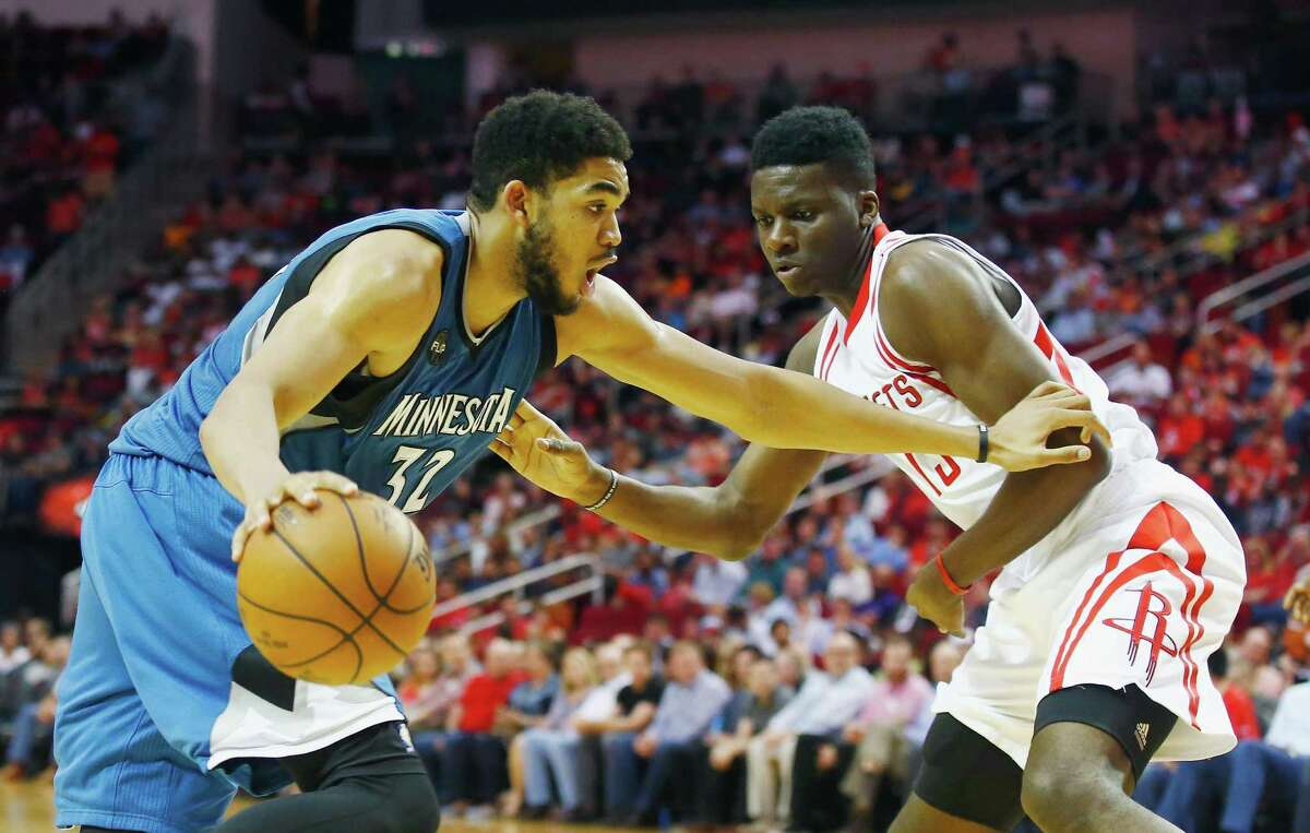 HOUSTON, TX - MARCH 18: Karl-Anthony Towns #32 of the Minnesota Timberwolves looks to drive with the basketball in front of Clint Capela #15 of the Houston Rockets during their game at the Toyota Center on March 18, 2016 in Houston, Texas. NOTE TO USER: User expressly acknowledges and agrees that, by downloading and or using this Photograph, user is consenting to the terms and conditions of the Getty Images License Agreement.