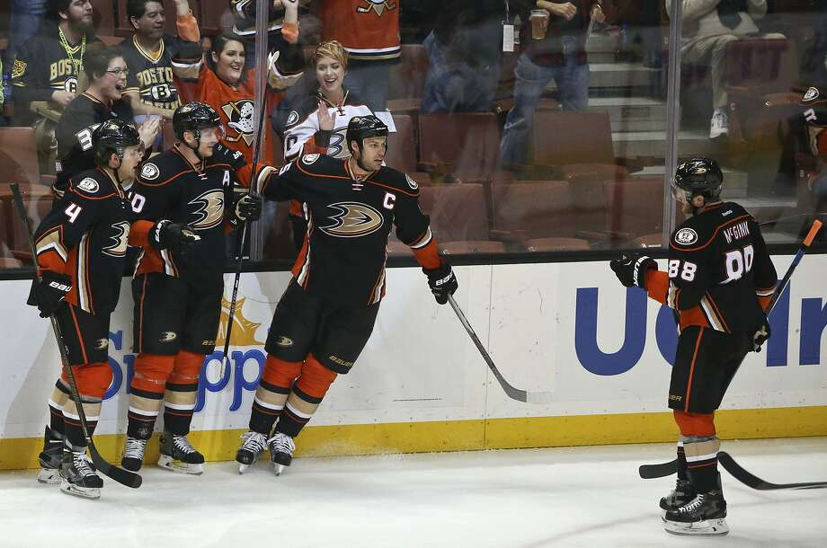 Anaheim Ducks' Cam Fowler, Corey Perry and Ryan Getzlaf, from left, celebrate as they await Jamie McGinn after McGinn's goal during the first period of an NHL hockey game against the Boston Bruins on Friday, March 18, 2016, in Anaheim, Calif. (AP Photo/Lenny Ignelzi) Photo: Lenny Ignelzi, AP