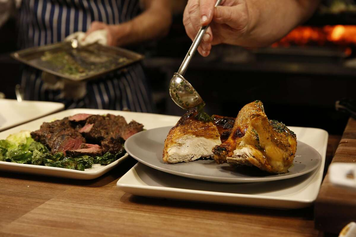Wood fire roasted chicken (right) and steak on opening night of Waxman restaurant at Ghirardelli Square in San Francisco, California on Friday March 18, 2016.