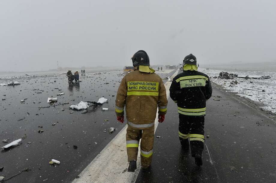A Russian Emergency Ministry employee  walk past the wreckage of a crashed plane at the Rostov-on-Don airport, about 950 kilometers (600 miles) south of Moscow, Russia Saturday, March 19, 2016. A Dubai airliner with 62 people on board nosedived and exploded in a giant fireball early Saturday while trying to land in strong winds in the southern Russian city of Rostov-on-Don, killing all aboard, officials said. (AP Photo) Photo: AP