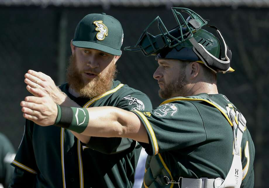 Oakland Athletics catcher Stephen Vogt, right, works with relief pitcher Sean Doolittle during spring training baseball practice in Mesa, Ariz., Sunday, Feb. 21, 2016. Vogt is shagging balls in the outfield, catching bullpens again and looking mobile running through agility drills on the side in a delightful mood as usual. (AP Photo/Chris Carlson) Photo: Chris Carlson, AP