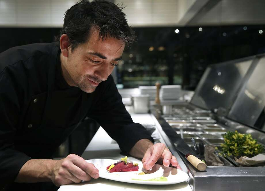 Matthew Dolan, chef at San Francisco's 25 Lusk, prepares escargot caviar and ahi tuna crudo with mustard blossoms, black salt and a green garlic mousse. Photo: Paul Chinn, The Chronicle