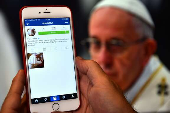 A man looks at the Instagram account of Pope Francis (Franciscus) on March 19, 2016 in Rome. The date for the pontiff's debut on the celebrity-dominated social medium was chosen by the 79-year-old himself as it marks the third anniversary of his inauguration as the leader of the world's 1.2 billion Catholics. / AFP PHOTO / GABRIEL BOUYSGABRIEL BOUYS/AFP/Getty Images
