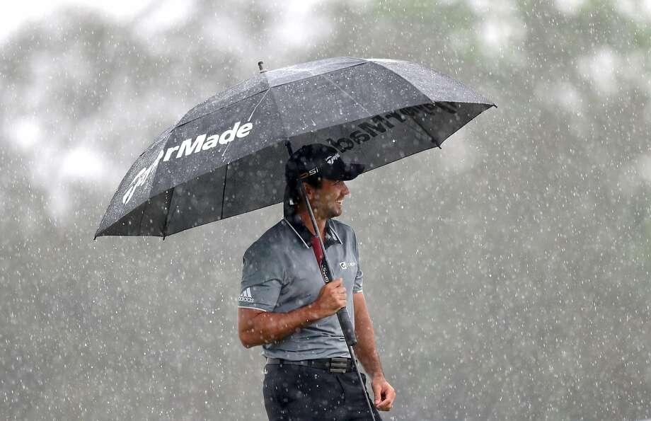 Jason Day waits to putt during a downpour. Photo: Willie J. Allen, Jr., AP