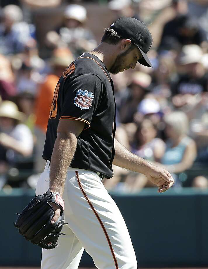 Madison Bumgarner walks off the mound Saturday after a Yonder Alonso single ends his day. Photo: Jeff Chiu, AP