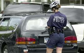 Greenwich 15 July 2004 - Police officer, Dhristy Gerard, writes a ticket for a double parked car on Greenwich Avenue. Photo/ Mel Greer COLOR