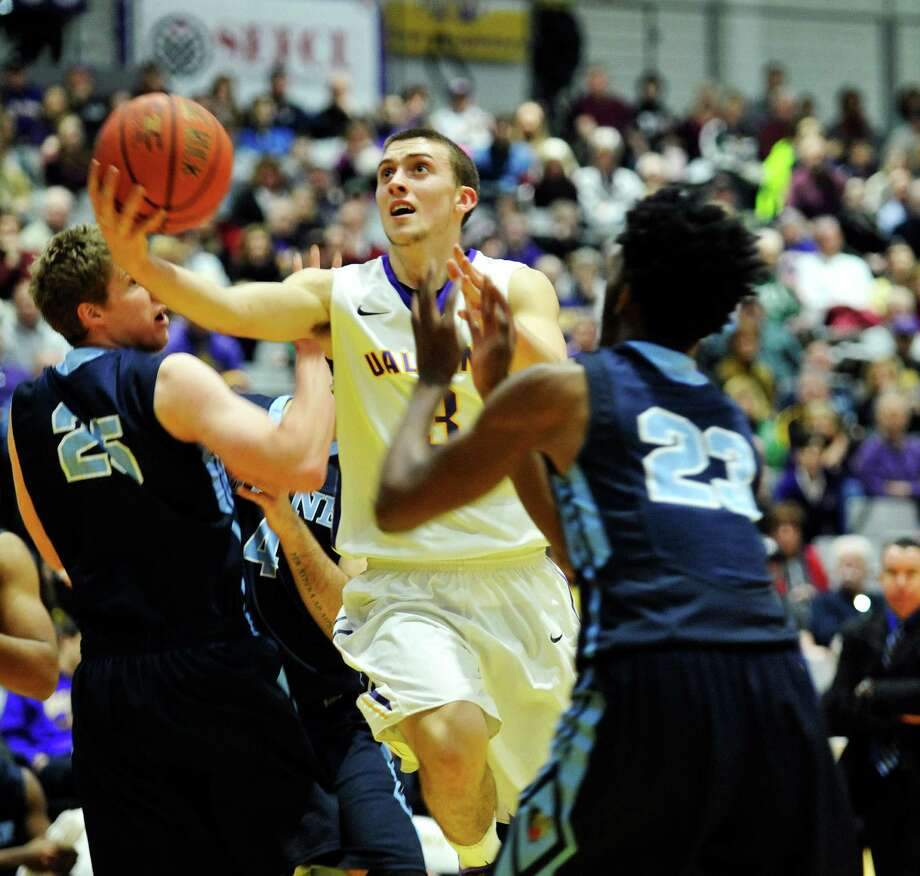 Joe Cremo of the UAlbany drives to the basket through two  Maine players during their game on Sunday, Feb. 14, 2016, in Albany, N.Y.  (Paul Buckowski / Times Union) Photo: PAUL BUCKOWSKI / 10035422A