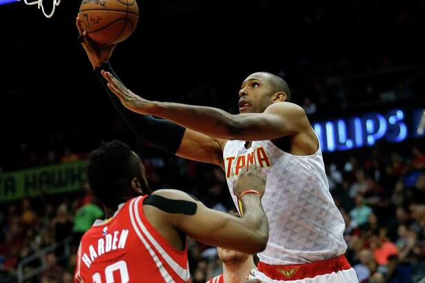 Atlanta Hawks center Al Horford (15) goes up for a shot against Houston Rockets guard James Harden (13) in the first half of an NBA basketball game  Saturday, March 19, 2016, in Atlanta.