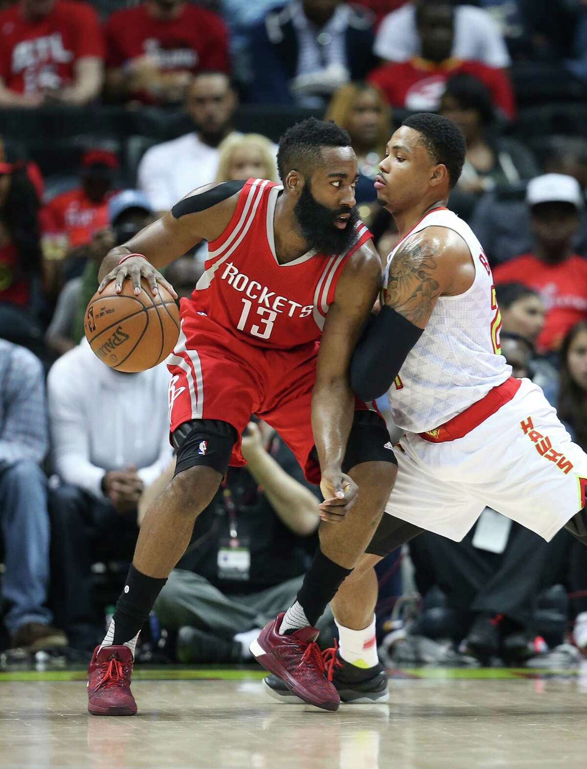 Houston Rockets guard James Harden (13) is guarded by Atlanta Hawks forward Kent Bazemore (24) in the first half of an NBA basketball game, Saturday, March 19, 2016, in Atlanta.