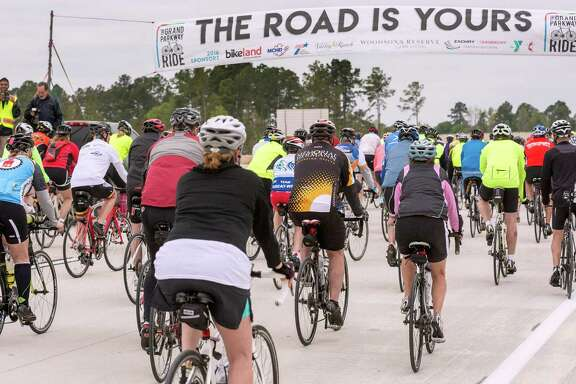 """Left: A banner greets bicyclists on what roadway officials call """"segment G"""" of the Grand Parkway, a stretch that will take motorists from Interstate 45 to Highway 59. The road is expected to open by month's end.   Right: Bicyclists westbound on the Grand Parkway pass a sign bearing its formal name, Texas 99."""