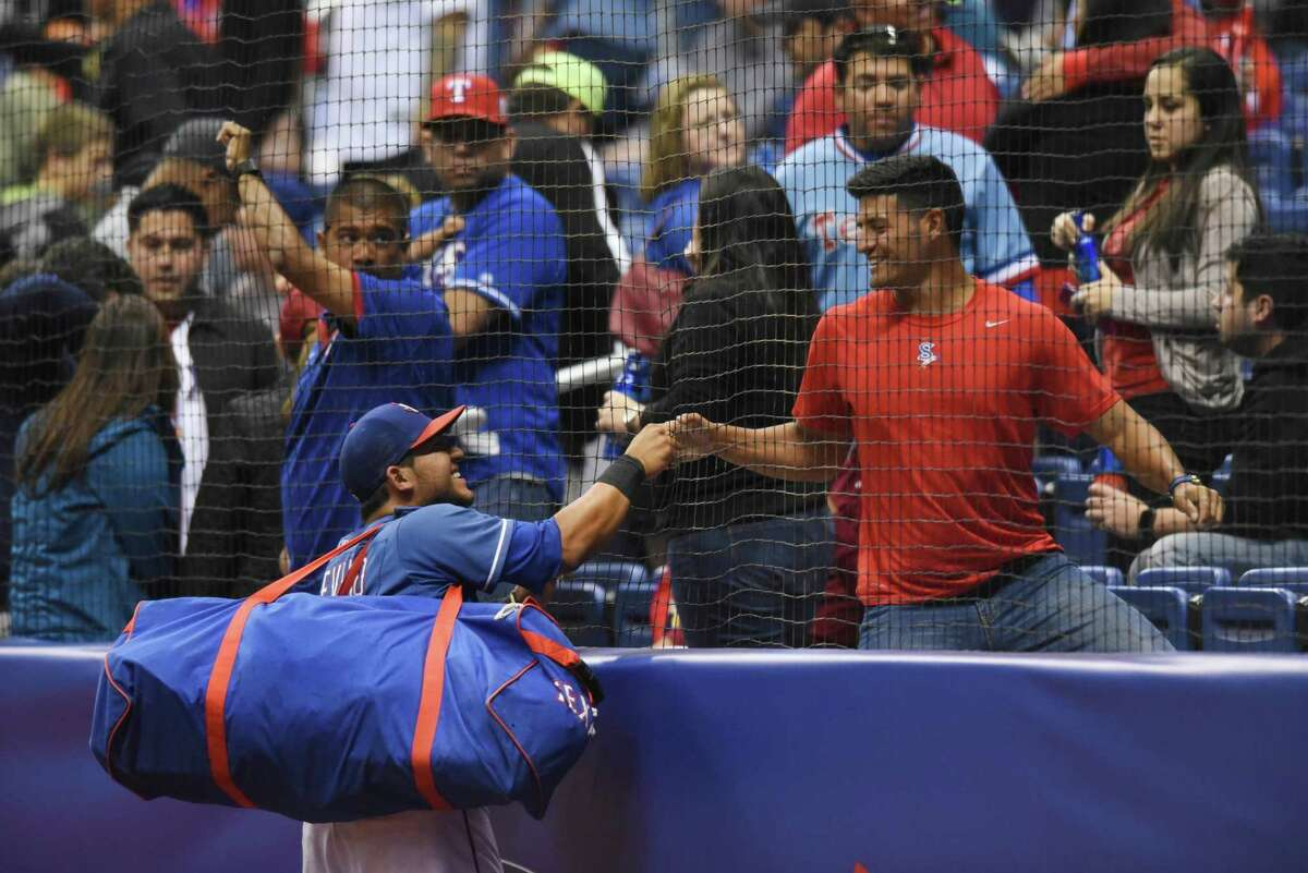 Texas Rangers catcher Jose Trevino greets fans after the Rangers defeated the Kansas City Royals, 13-6, during Big League Weekend action at the Alamodome on March 19, 2016.