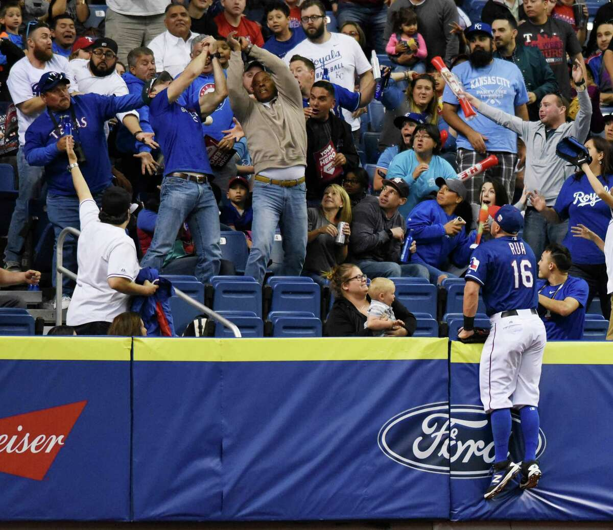Texas Rangers outfielder Ryan Rua watches as fans attempt to catch a home-run ball during Big League Weekend action against the Kansas City Royals at the Alamodome on March 19, 2016.