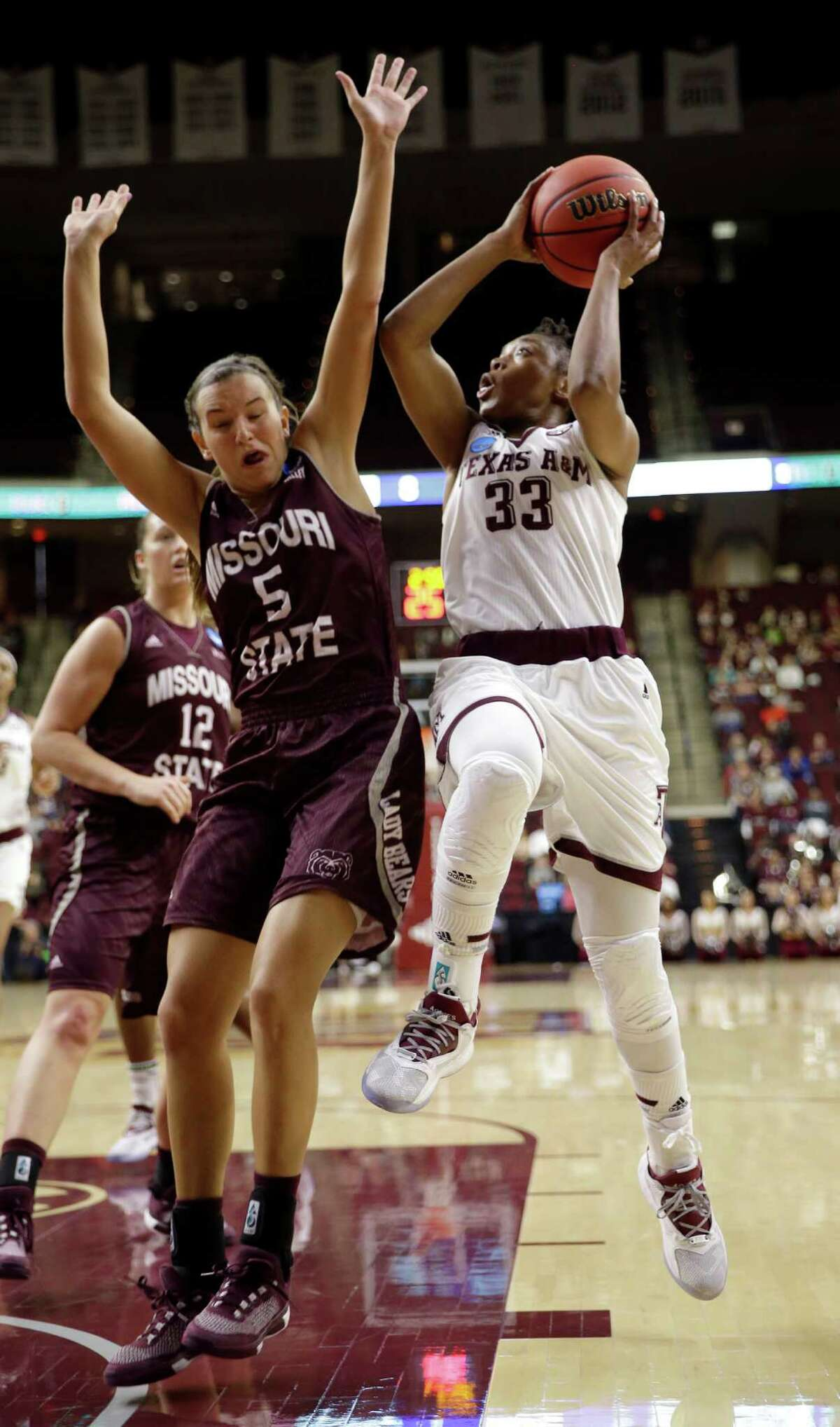 Texas A&M's Courtney Walker, right, goes up for two of her 29 points despite the defensive efforts of Missouri State's Liza Fruendt on Saturday.