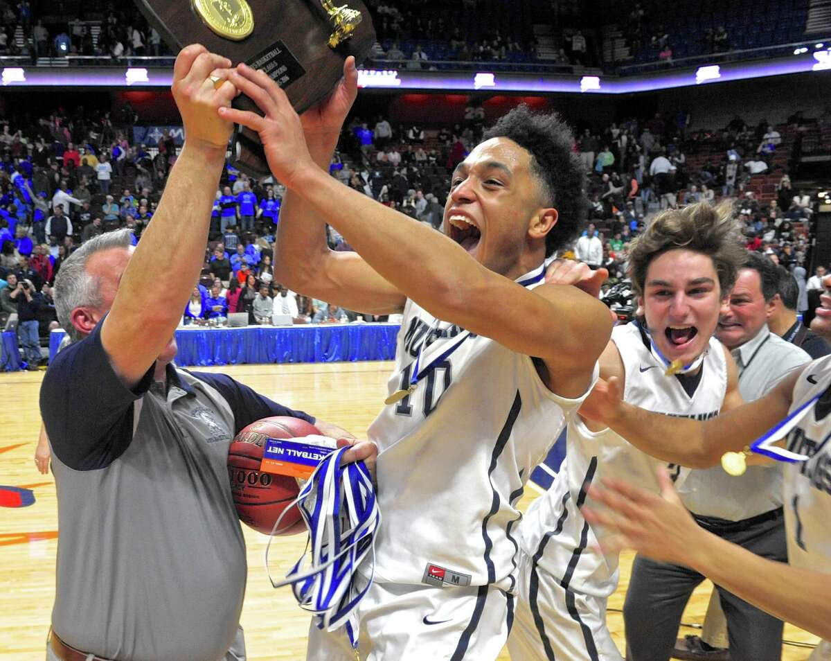 Immaculate head coach Nelson Mingachos, left, and senior guard Darius Smith (10) hold the Class S boys basketball championship trophy as their team runs out to meet them on the floor after Immaculate defeated Coginchaug 53-43 on Saturday at Mohegan Sun Arena in Uncasville.