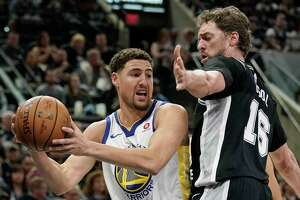 Golden State Warriors' Klay Thompson, left, looks to pass around San Antonio Spurs' Pau Gasol during the first half of Game 4 of a first-round NBA basketball playoff series in San Antonio, Sunday, April 22, 2018, in San Antonio. (AP Photo/Darren Abate)