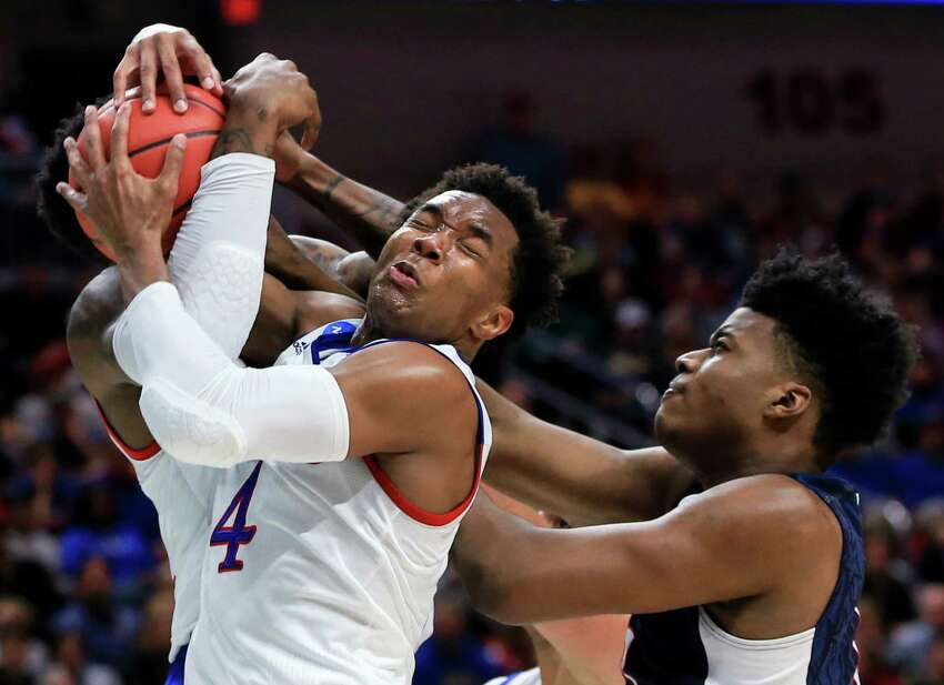Connecticut's Steven Enoch, right, loses a rebound to Kansas' Wayne Selden Jr. (1), and Jamari Traylor, left rear, during a second-round men's college basketball game in the NCAA Tournament in Des Moines, Iowa, Saturday, March 19, 2016.