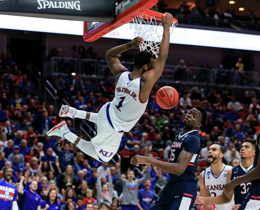 Kansas' Wayne Selden Jr. (1) hangs on to the rim after dunking over Connecticut's Amida Brimah (35), with Perry Ellis (34) and Shonn Miller (32) watching, during a second-round men's college basketball game in the NCAA Tournament in Des Moines, Iowa, Saturday, March 19, 2016. Kansas won 73-61.