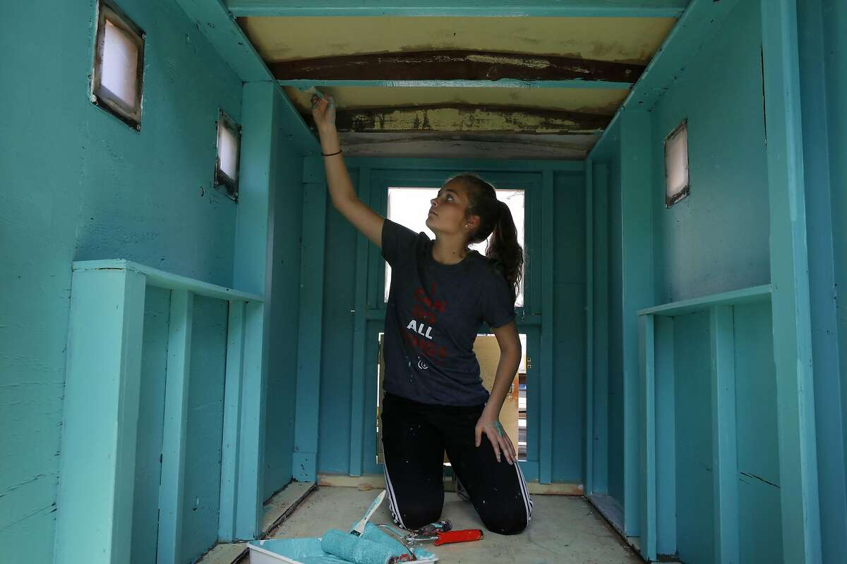 Reilly Chabino, 15, paints a tiny home while working with other members of the Carmichael Presbyterian Church youth group as volunteers for Greg Kloehn to build multiple tiny homes March 19, 2016 at Nimby in Oakland, Calif. The houses will eventually be given to homeless people in the area.