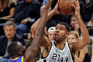San Antonio Spurs' Tim Duncan shoots around Golden State Warriors' Draymond Green during first half action Saturday March 19, 2016 at the AT&T Center.