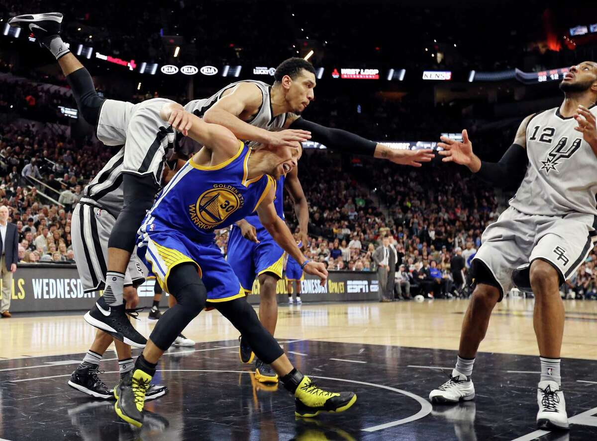San Antonio Spurs' Danny Green falls on Golden State Warriors' Stephen Curry after Curry shot the ball as LaMarcus Aldridge eyes the rebound during second half action Saturday March 19, 2016 at the AT&T Center. The Spurs won 87-79.