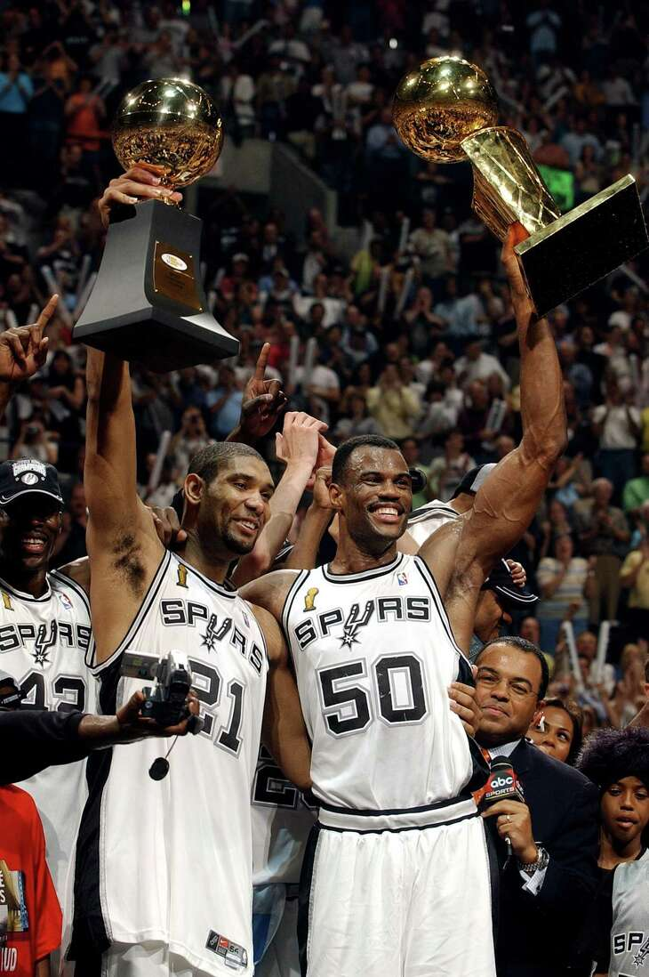Spurs Tim Duncan with MVP trophy and David Robinson with Larry O'Brien championship trophy celebrate their NBA Championship after game six of the NBA Finals at SBC Center in San Antonio on Sunday, June 15, 2003. ( JERRY LARA STAFF )