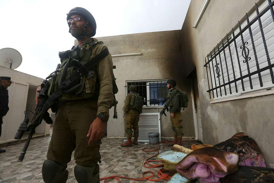 Israeli forces patrol outside the home that was set ablaze in the West Bank village of Duma. Photo: JAAFAR ASHTIYEH, AFP/Getty Images