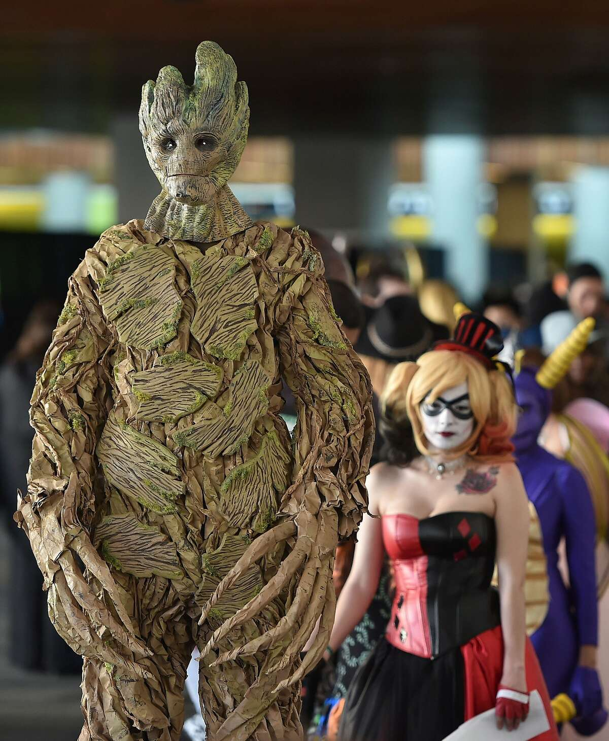 Dressed as Groot, Dan Collins (L) waits in line to be pre-judged for a costume contest at the Silicon Valley Comic Con in San Jose, California on March 19, 2016. The comic and entertainment-themed event features exhibits, panel discussions and pop culture artistry.