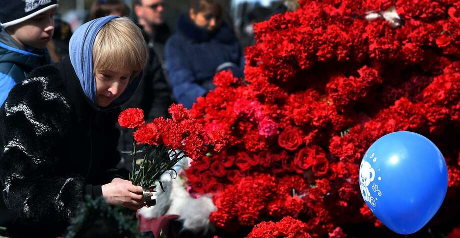 A woman lays flowers in tribute to the 62 people who died when a FlyDubai jetliner nose-dived and crashed Saturday in the Russian city of Rostov-on-Don. Photo: VASILY MAXIMOV, AFP/Getty Images