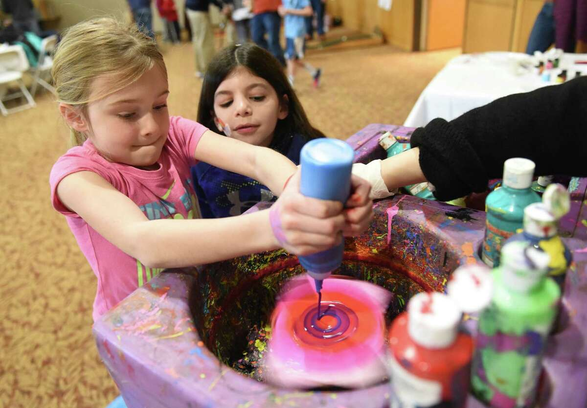 Seven-year-olds Hannah Winig, left, of Greenwich, and Lexi Hoenig, of Cos Cob, create colorful spin art during the Purim Carnival at Temple Sholom in Greenwich, Conn. Sunday, March 20, 2016. Dozens of kids dressed in costume celebrated Purim with food and a variety of activities ranging from a bounce house to spin art. In the Jewish faith, Purim commemorates the saving of the Jewish people from Haman.