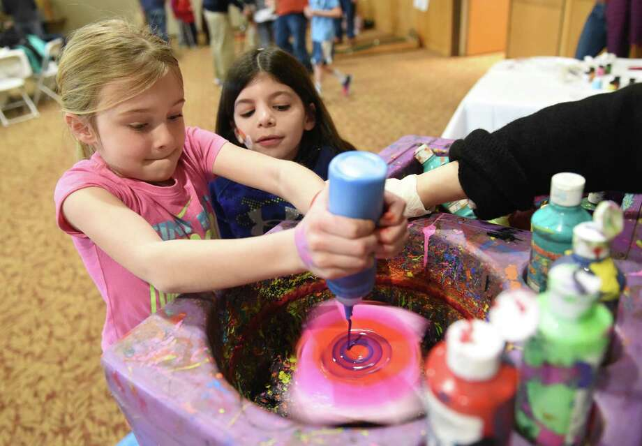 Seven-year-olds Hannah Winig, left, of Greenwich, and Lexi Hoenig, of Cos Cob, create colorful spin art during the Purim Carnival at Temple Sholom in Greenwich, Conn. Sunday, March 20, 2016. Dozens of kids dressed in costume celebrated Purim with food and a variety of activities ranging from a bounce house to spin art. In the Jewish faith, Purim commemorates the saving of the Jewish people from Haman. Photo: Tyler Sizemore / Hearst Connecticut Media / Greenwich Time