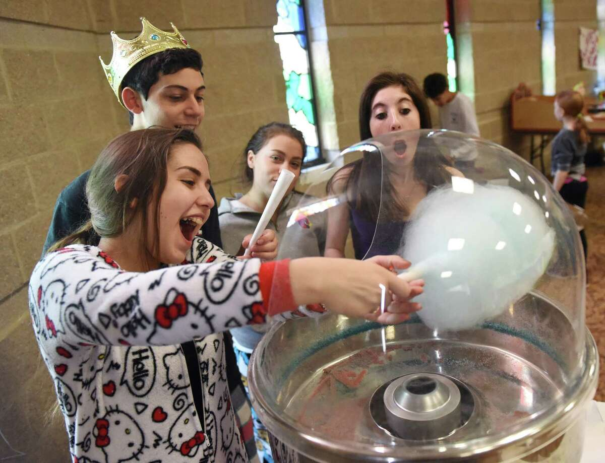From left, Gaia Sarfati, 15, of Greenwich, Jordan Bellin, 15, of Rye Brook, N.Y., Shira Mann, 14, of Greenwich, and Zoe Cohen, 15, of Rye Brook, N.Y., make a gigantic cotton candy during the Purim Carnival at Temple Sholom in Greenwich, Conn. Sunday, March 20, 2016. Dozens of kids dressed in costume celebrated Purim with food and a variety of activities ranging from a bounce house to spin art. In the Jewish faith, Purim commemorates the saving of the Jewish people from Haman.