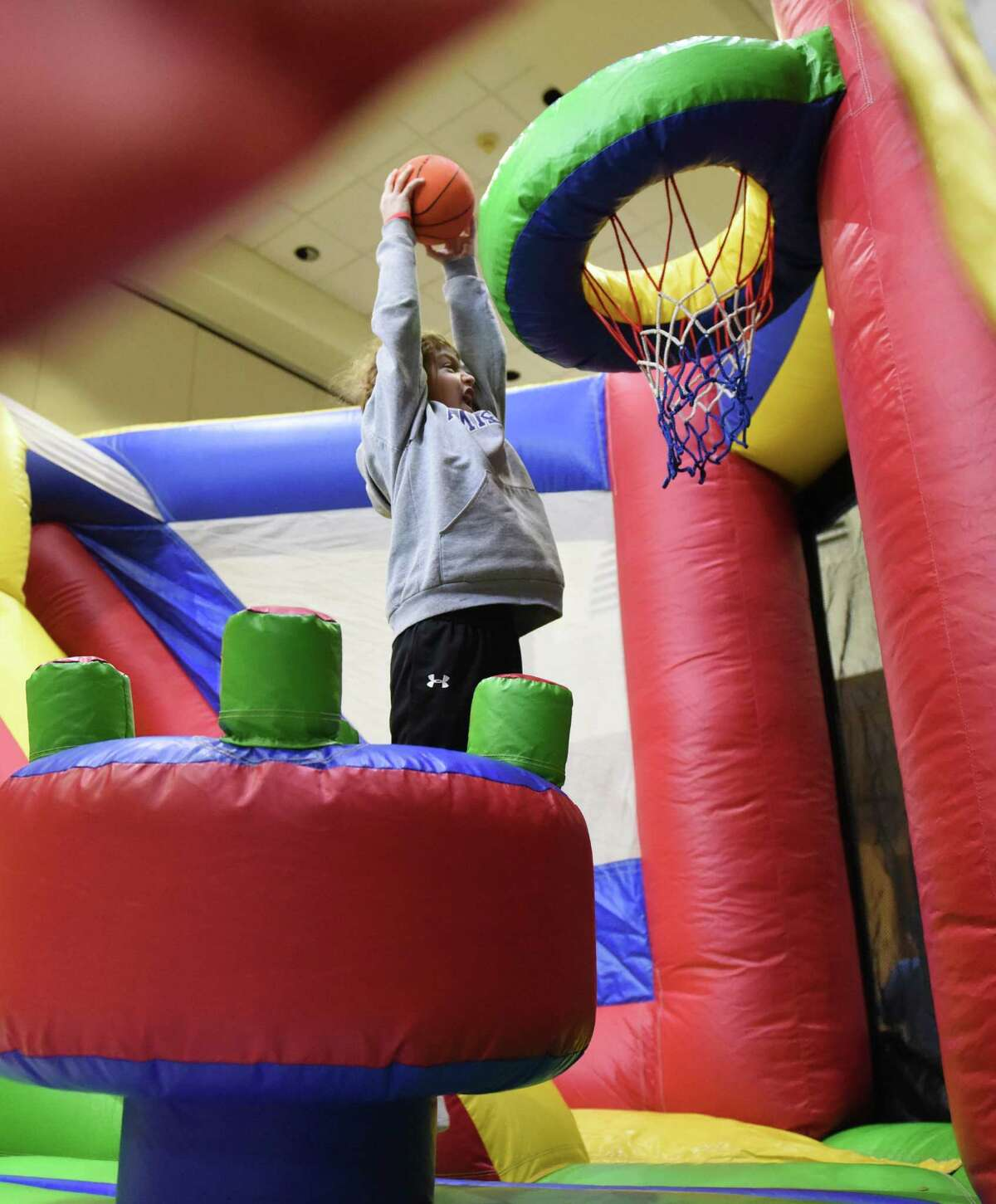 Max Raff, 9, of Armonk, N.Y., dunks a basketball in the bouncehouse at the Purim Carnival at Temple Sholom in Greenwich, Conn. Sunday, March 20, 2016. Dozens of kids dressed in costume celebrated Purim with food and a variety of activities ranging from a bounce house to spin art. In the Jewish faith, Purim commemorates the saving of the Jewish people from Haman.