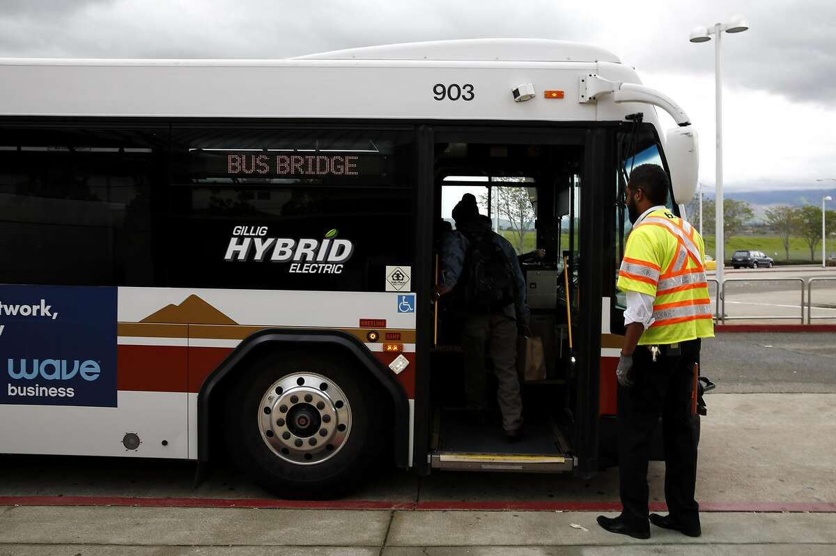Phaethon Brown of BART helps a man board a bus that will connect him to the Pittsburg/Bay Point station from the North Concord/Martinez Station in Concord, California, on Sunday, March 20, 2016.
