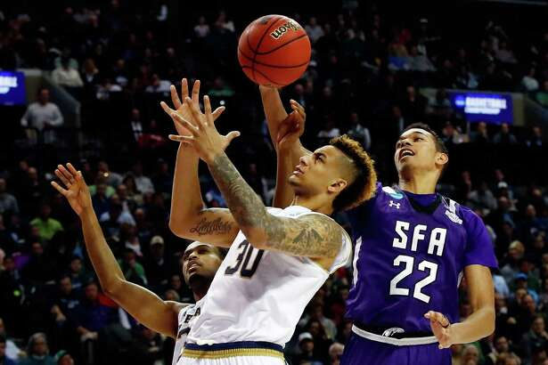 NEW YORK, NY - MARCH 20:  V.J. Beachem #3 and Zach Auguste #30 of the Notre Dame Fighting Irish batte for posession with T.J. Holyfield #22 of the Stephen F. Austin Lumberjacks in the second half during the second round of the 2016 NCAA Men's Basketball Tournament at Barclays Center on March 20, 2016 in the Brooklyn borough of New York City.