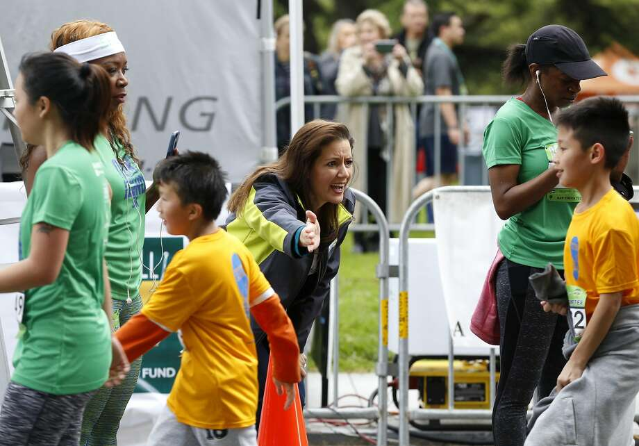 Mayor Libby Schaaf reaches out to high-five a young participant finishing his race at the Oakland Running Festival. Photo: Connor Radnovich, The Chronicle