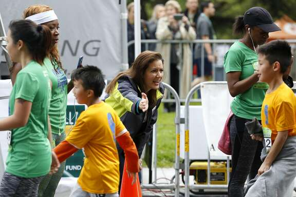 Oakland Mayor Libby Schaaf reaches out to high-five a kid after he finished his race at the Oakland Running Festival in Oakland, California, on Sunday, March 20, 2016.