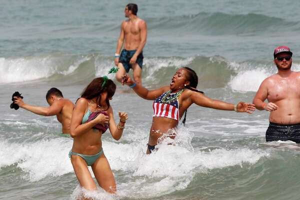Ynesha Autumn Franklin, second from right, reacts to a wave striking her Thursday March 17, 2016 at South Padre Island, Texas. (Nathan Lambrecht/The Monitor via AP) MAGS OUT; TV OUT; MANDATORY CREDIT