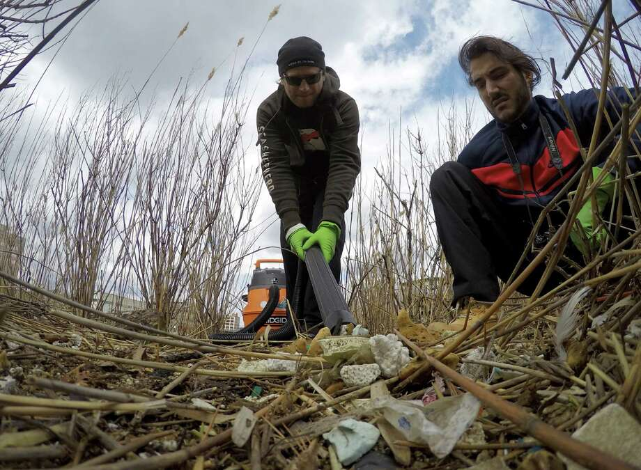 David Michel and Dave Leute, both of Stamford, use a high powered shop vacuum to clean polystyrene bits out of the marsh areas at Czescik Marina on March 18, 2016 in Stamford. Michel is spearheading a group of volunteers to rid the area of garbage and restore the marshlands to its natural habitat. Photo: Matthew Brown / Hearst Connecticut Media / Stamford Advocate