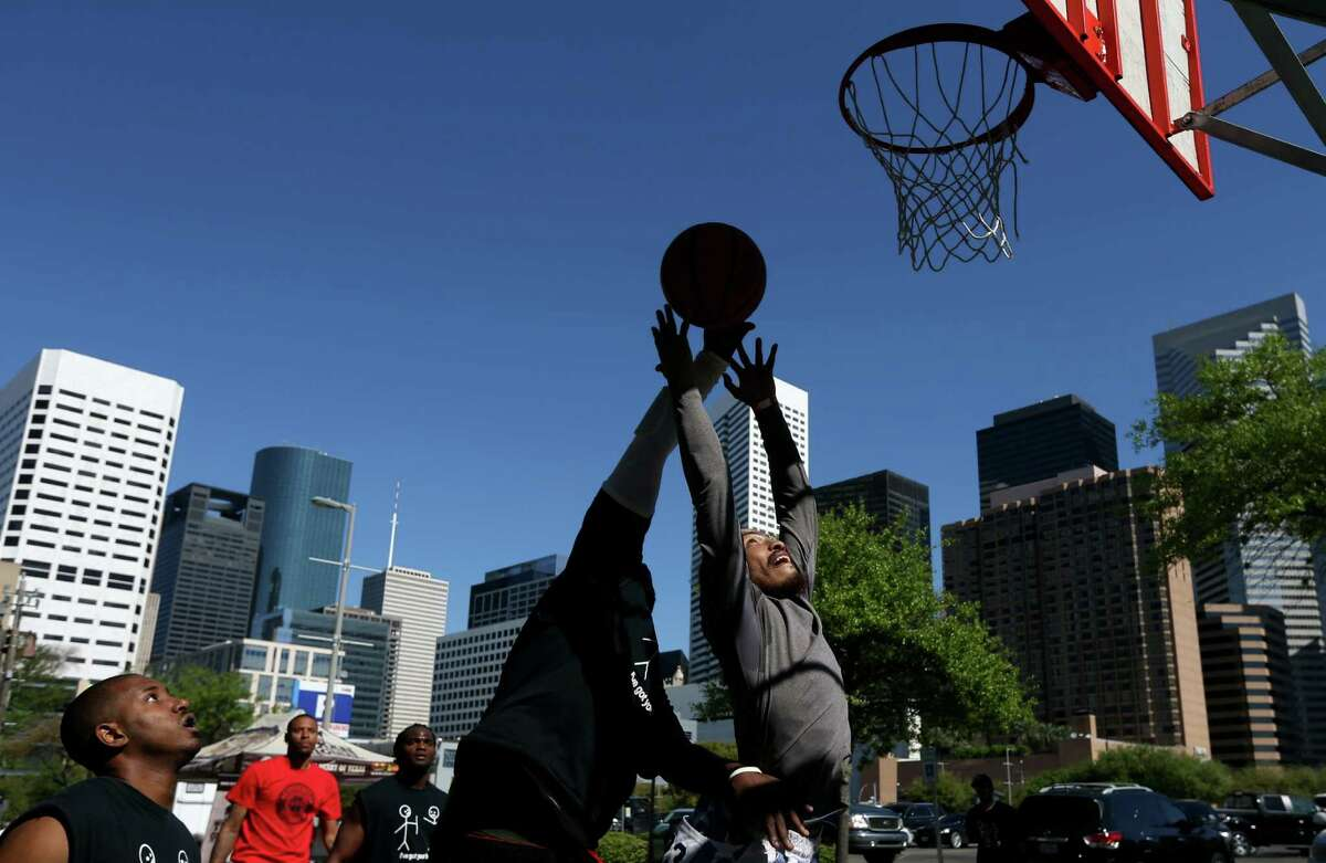 Maurice Jefferson, left, of team Deez Nuts from New Orleans, blocks the shot of Ramon Gomez, of team Fab Five from Houston, during the second round of the Adult Recreation division in the 12th annual Blacktop Battle hosted by the Houston Rockets, Sunday, March 20, 2016, in Houston, Texas. Blacktop Battle is the largest 3-on-3 basketball tournament in Texas and takes place on the streets surrounding Toyota Center.
