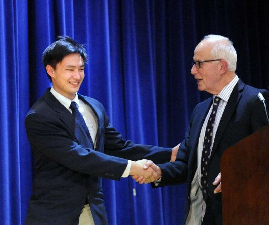 Greenwich High School senior Stephen Song accepts the 2015 Fleishman Service Award from former Superintendent Ernest Fleishman during the 2015 Community Service Awards ceremony at Western Middle School. Photo: File Photo